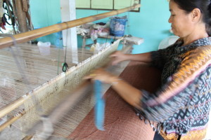 Weaver is weaving natural dyed fabrics