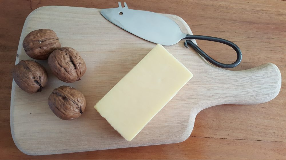 cheese knife on timber board with cheese and walnuts